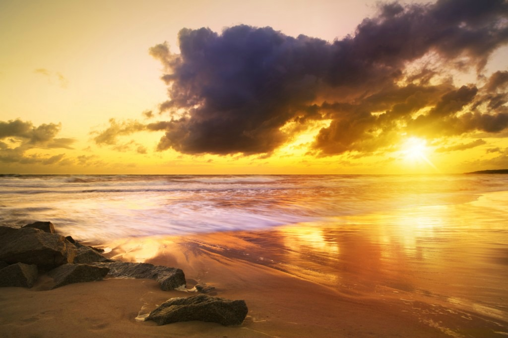 "On a ""Sea Beach During Colorful Sunset"" is a soulful way to enjoy a quiet travel adventure in a coastal city. Image of the same name is by @iStockphoto/konradlew."