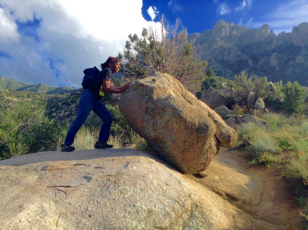 """SuperMel """"pushes"""" a boulder on the Pine Tree Trail, an Aguirre Springs scenic hike."""