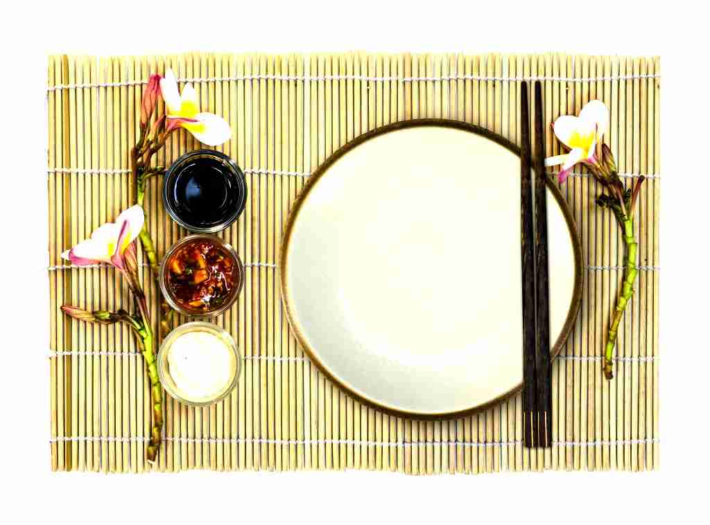 Table setting for Japanese food with copper-rimmed white dinner plate and hashi (chopsticks) atop a maki placemat.