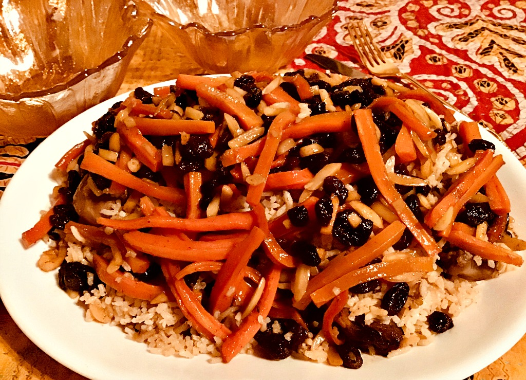A white platter laden with Qabili Palau, the national dish of Afghanistan: carrot, black raisins, almond slivers, and basmati rice atop chicken.