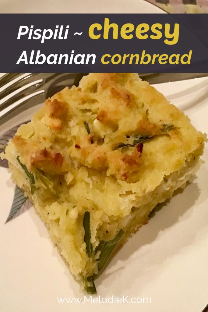 Slice of Pispili ~ cheesy Albanian cornbread atop a cream-colored dish.
