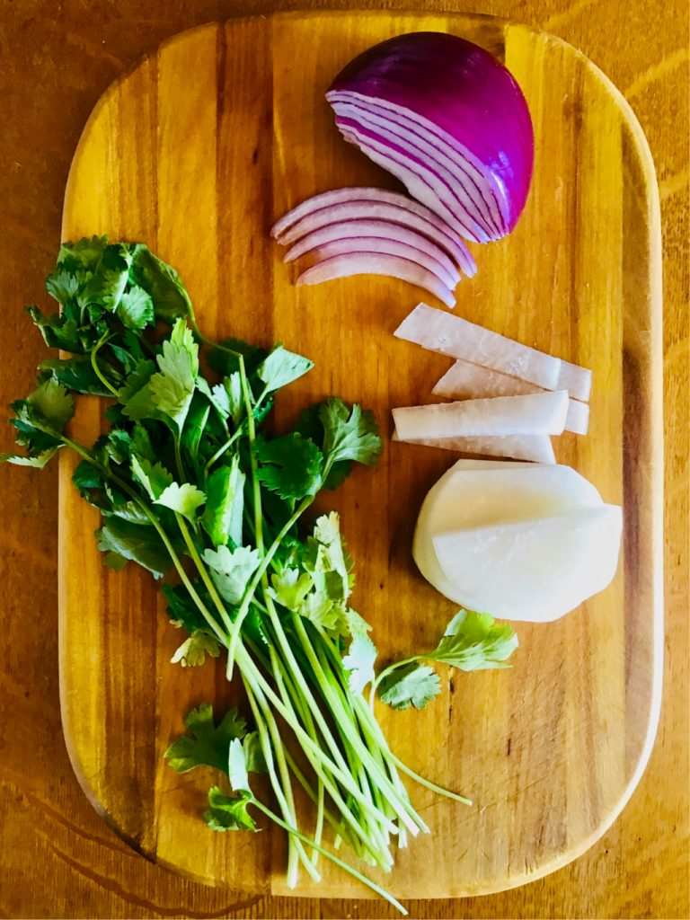 The ingredients for Hawaiian chicken salad, in its various versions, often include cilantro, onions, and daikon or cucumber.