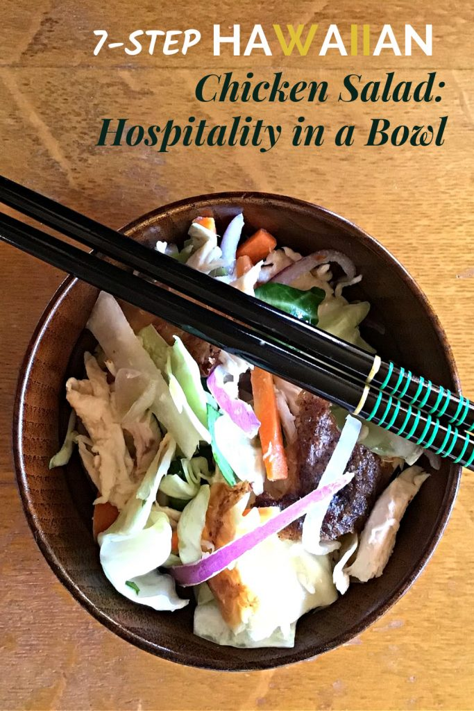 Hawaiian Chicken Salad in a wooden bowl topped with a pair of black chopsticks atop a wooden table.